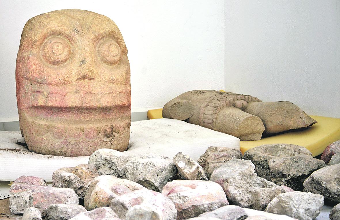 Az emberfejet ábrázoló szobor és egy törzs, ez utóbbi valószínűleg magát a Sipe-Totek (Megnyúzott urunk) néven ismert termékenységistent ábrázolja